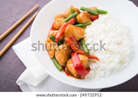 Spicy chicken with vegetables ( green beans and red pepper) and rice. Oriental food. - stock photo