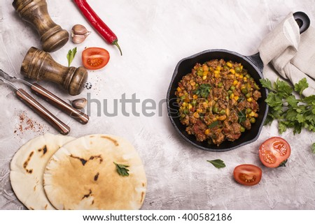 Spicy chili con carne with kidney bean and ground beef and ingredients over stone table. Top view - stock photo