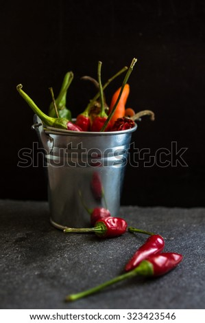 Spicy chili peppers on the black background. Selective focus - stock photo
