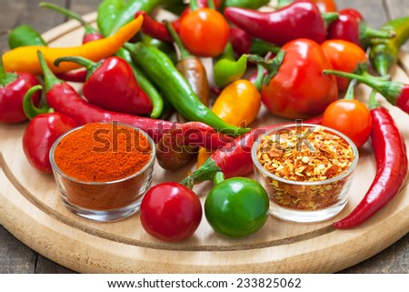 Spicy chili peppers on wooden board - stock photo