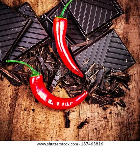 Spicy Chocolate Bar on wooden background closeup. Chunks of Broken dark chocolate bar on wood table macro. - stock photo
