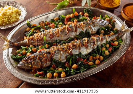 Spicy cooked mackerel fish stuffed with spices and garnished with vegetables and garbanzo beans in large silver platter - stock photo