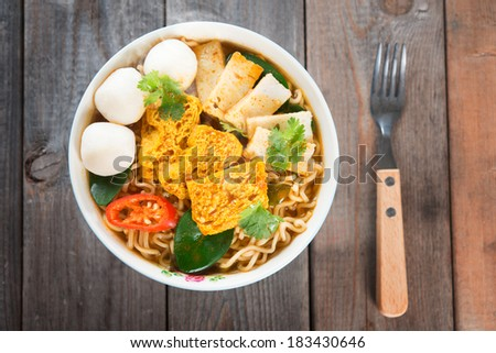 Spicy curry instant noodles soup with fork on wooden dining table. Fresh hot with steamed smoke. - stock photo