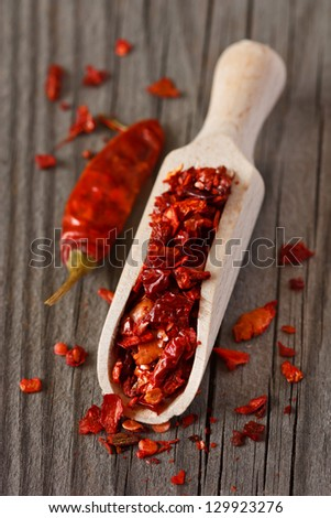 Spicy dry chili in a wooden scoop.