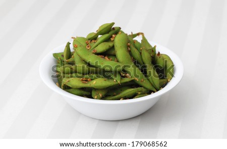 Spicy Edamame - Cooked and spiced soybean pods in a white bowl. - stock photo