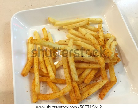 spicy french fries on white dish in restaurant, Thailand