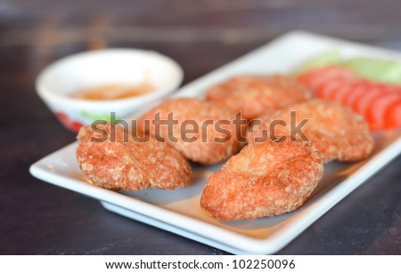 Spicy fried fish cake (Tod Mun Pla) served with cucumber , tomato and  sweet sauce - stock photo