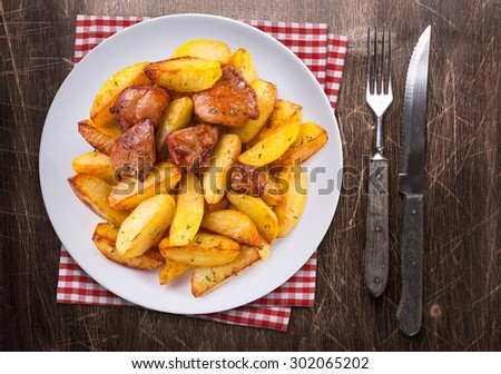 Spicy fried potatoes with herbs and spices served in white plate. Top view on wooden table. Fork, knife and towel. - stock photo