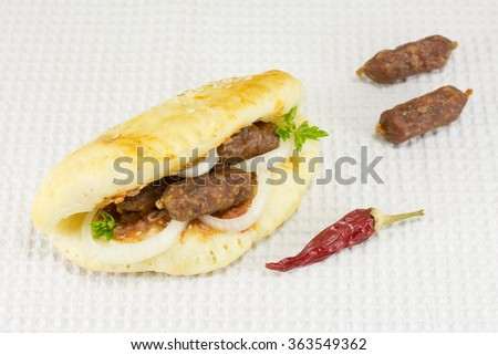 Spicy gourmet sandwich with special small sausages on white tablecloth - stock photo