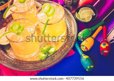 Spicy grapefruit margarita cocktail garnished with lime and jalapenos.
