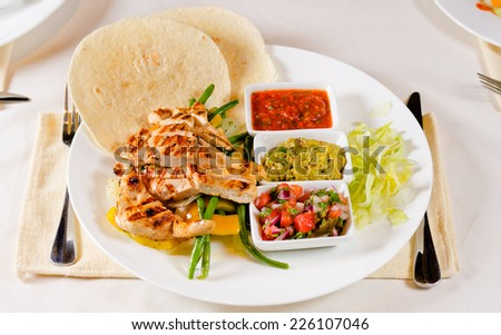 Spicy grilled chicken fajitas with hot chili and tomato salsa, dipping sauces and corn tortillias, high angle view - stock photo