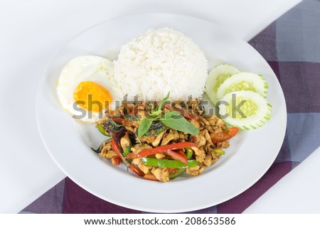 Spicy ground meat over rice with sauteed chopped, fresh chili and garlic, bell pepper, basil leaf, fried egg and cucumber - stock photo