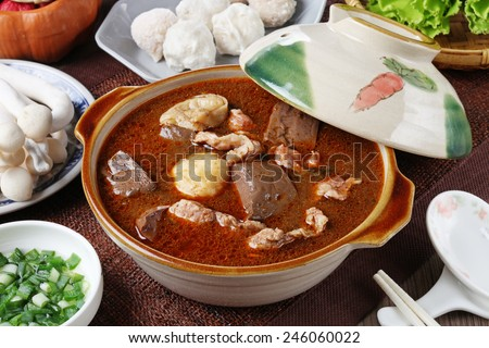 Spicy  hot pot with pork, tofu,  mushrooms and green leaves  - stock photo