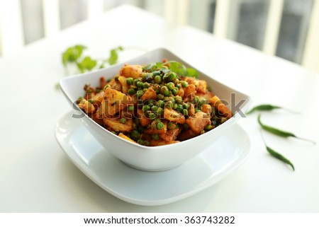 Spicy Indian Dish of Potatoes and Peas - stock photo