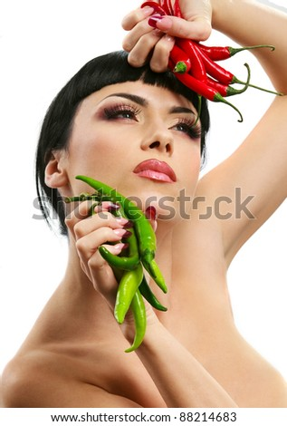 Spicy lady holding red and green hot chilli peppers in arms isolated on white background - stock photo