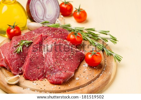 Spicy meat in salt and pepper on a round plate, tomatoes, and ingredients for frying - stock photo