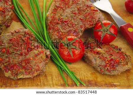spicy meat on wood with pepper and chives - stock photo