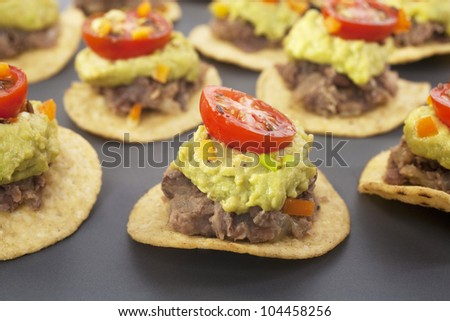 Spicy Mexican party food, corn chips topped with refried beans, avocado and tomato salsa. - stock photo