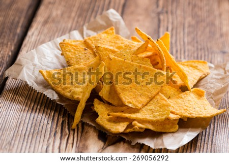 Spicy Nachos (close-up shot) on rustic wooden background - stock photo