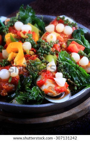 Spicy New Zealand Mussel with fried basil, Fresh Green Peppercorns served on Hot Plate, Thai Style. - stock photo