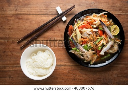 spicy papaya salad with crab and thai Vermicelli, chopsticks, on wooden table, Thai food - stock photo