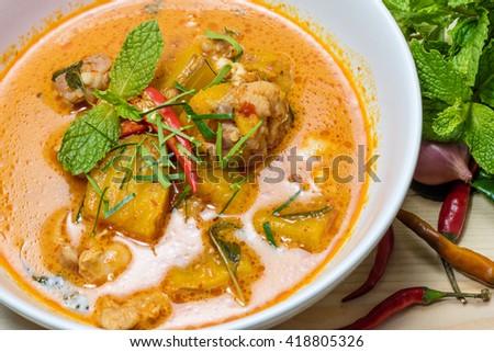 spicy pork pumpkin curry on the wooden floor - stock photo