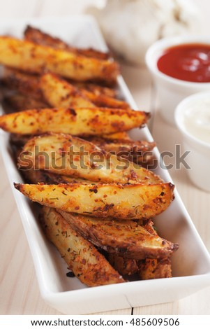 Spicy roasted potato wedges with onion sauce and  salsa dip