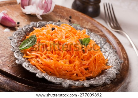 Spicy salad Asian style with carrots, garlic, red and black pepper,  coriander. Selective focus. Rustic style. - stock photo