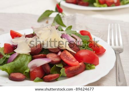 Spicy Salad with chorizo sausage, cherry tomato and parmesan - stock photo