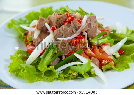 Spicy salad with pork and green herb in Thai style - stock photo