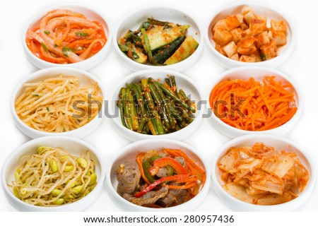Spicy salads of traditional Korean cuisine: soy sprouts, bamboo shoots, chicken ventricles, chimchi, raw potatoes, carrots, boiled squid, cucumbers and zucchini. - stock photo