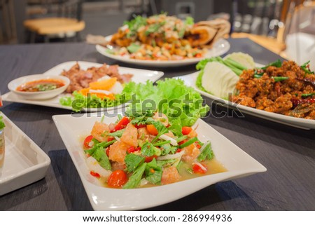 Spicy salmon salad with mixed vegetable and grill pork and spicy crispy pork - stock photo