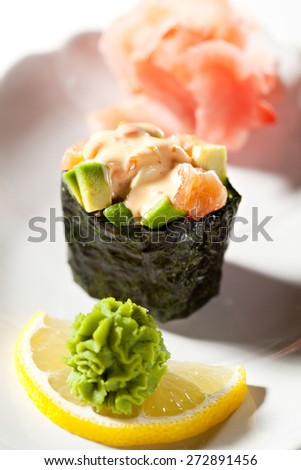 Spicy Salmon with Avocado Gunkan Sushi. Garnished with Ginger and Wasabi - stock photo