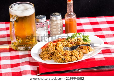 Spicy Shrimp and Chicken Jambalaya in typical Cajun Restaurant Setting.  Bright light from right rear adds emphasis to condensation on beer mug. - stock photo