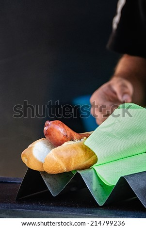 Spicy, smoked sausage hotdog for sale, male street vendor's hand in background. Typical local street food, Prague, Czech Republic. Selective focus, low key lighting. - stock photo