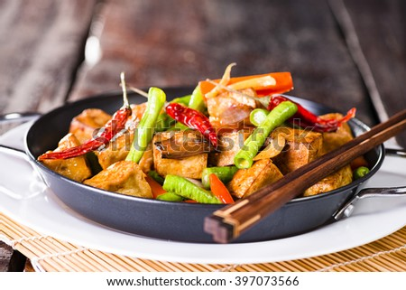 Spicy snack of fresh roast vegetables and tofu in a bowl on a rustic dark brown wooden table