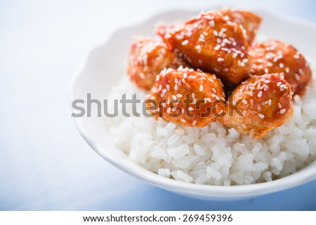 Spicy sweet and sour chicken with sesame and rice on blue wooden background close up. Oriental food. - stock photo