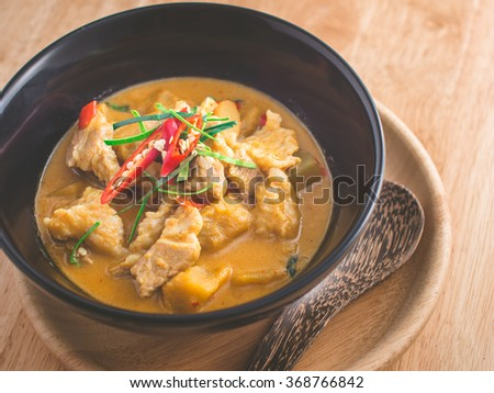 Spicy Thai food. Delicious red curry with pork and pumpkin on black bowl. Warm light tone and add vignette. - stock photo