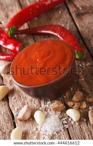 Spicy Thai Sriracha sauce with ingredients close-up on the table. vertical