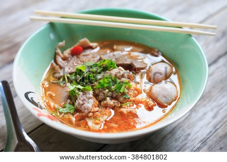 Spicy TOM YAM pork noodle soup on wooden table - stock photo