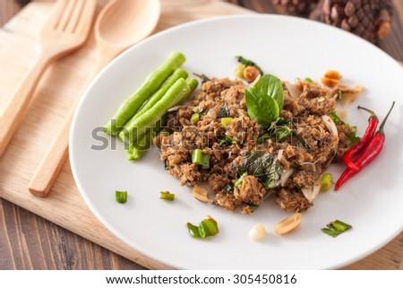 Spicy tuna salad on wood background - stock photo