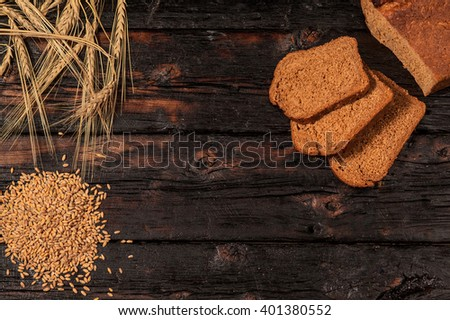 Spikelets of wheat and rye bread on a wooden table - stock photo