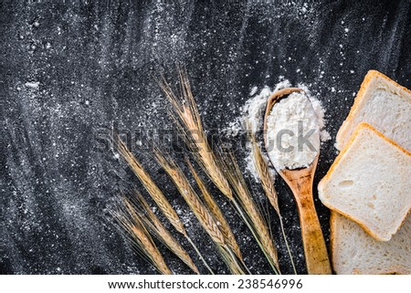 spikelets of wheat, bread and spoon with flour  on a black  textured table - stock photo