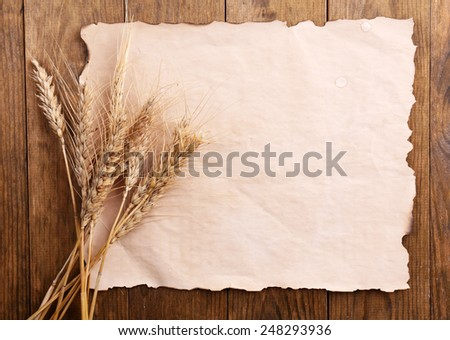 Spikelets of wheat with paper on wooden background - stock photo