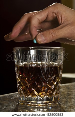 Spiking a drink with a Ruffee (Rohypnol) - stock photo
