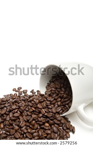 spill the beans - white coffee cup with whole coffee beans spilt on white background. closeup with limited dof. - stock photo