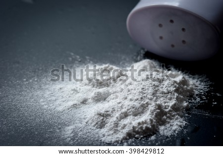 Spilled baby scented powder on a black slate,Selective focus