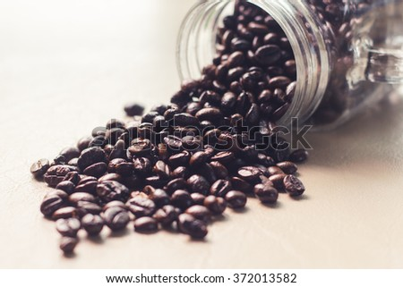 Spilled coffee beans from the Mason jar on the leather texture. - stock photo