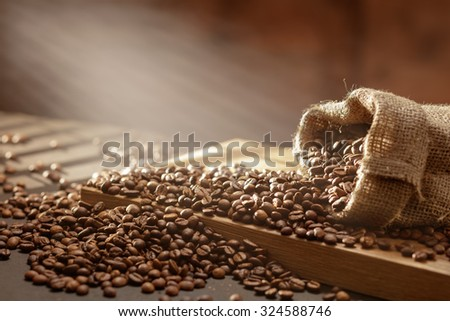 spilled coffee beans in bag on wooden table. Morning light - stock photo