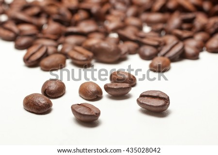 spilled coffee beans on white background, close up